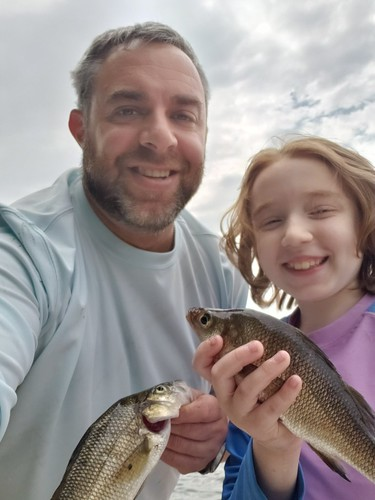 Photo of man and his daughter each holding a white perch