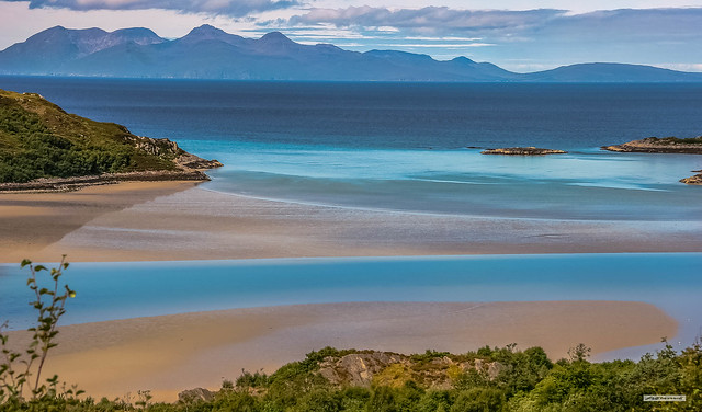 Salmon pink sands and azure blues of Morar Bay and the Isle of Rum from Morar Cross, Inverness-shire, Scotland.