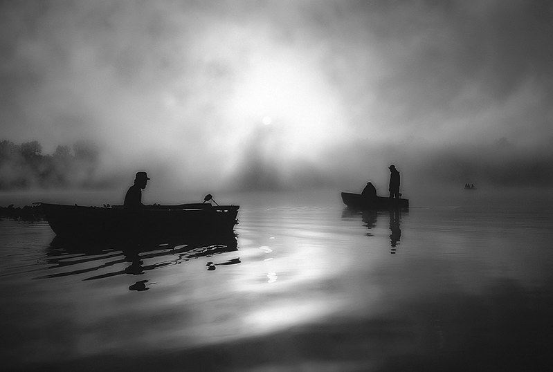 Sunrise at Lake Cassidy with Cascade foothills in fog with silhouetted fishermen