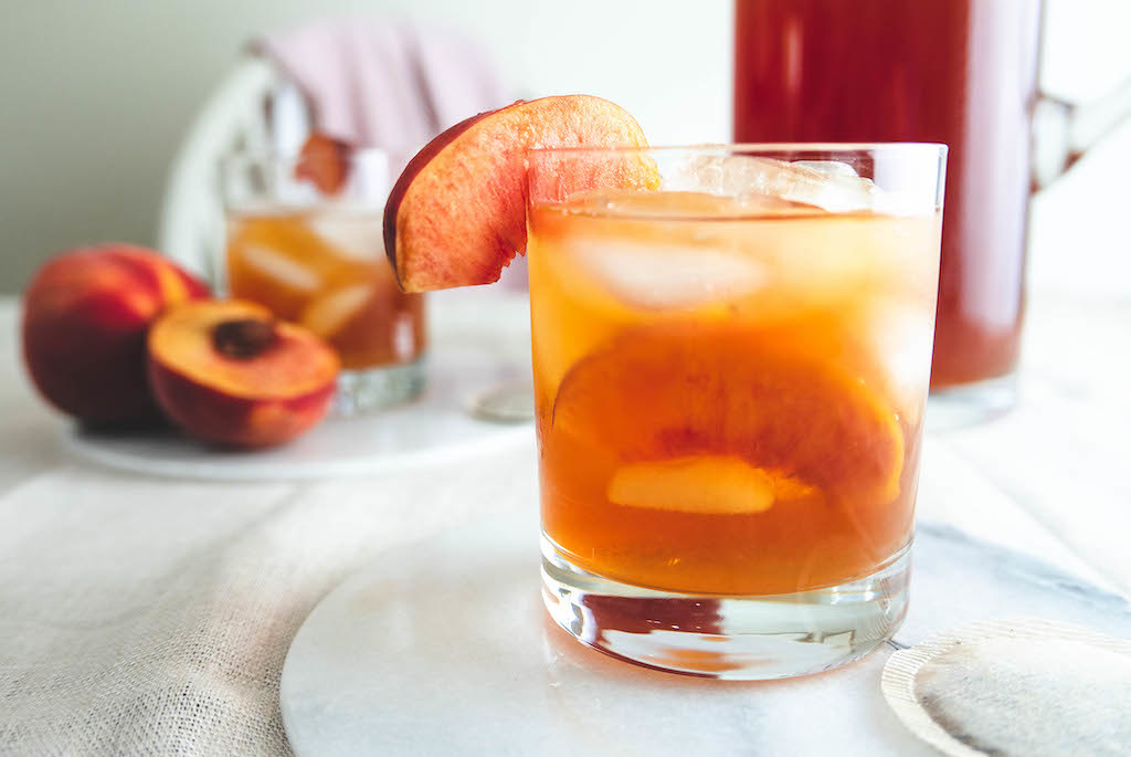 A side shot of the peach cocktail. A pitcher and peaches sit in the background.