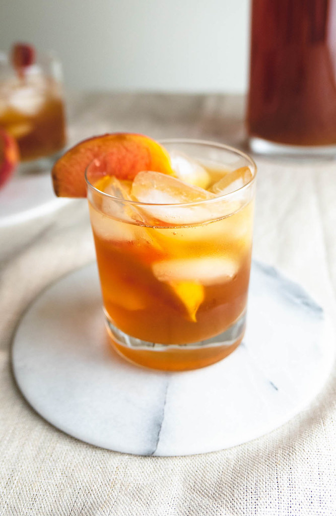 A side shot of peach sweet tea and bourbon cocktail.