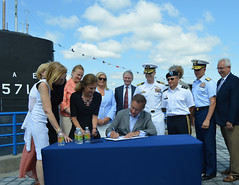State Reps. Kathleen McCarty and Holly Cheeseman, and State Senators Osten and Somers joined dignitaries and naval personnel as Governor Lamont signs legislation into law at the Submarine Base in Groton.  The legislation, HB 6449 (Public Act 21-152)¸ An Act Expanding Economic Opportunity in Occupations Licensed by the Departments of Public Health and Consumer Protection¸ makes it easier for professionals in a number of fields who are licensed in other states to obtain Connecticut credentials if they have residency in the state. Particularly, this is meant to assist the spouses of service members who are permanently stationed in Connecticut. Individuals seeking a license to practice in Connecticut must meet certain experience and background requirements.