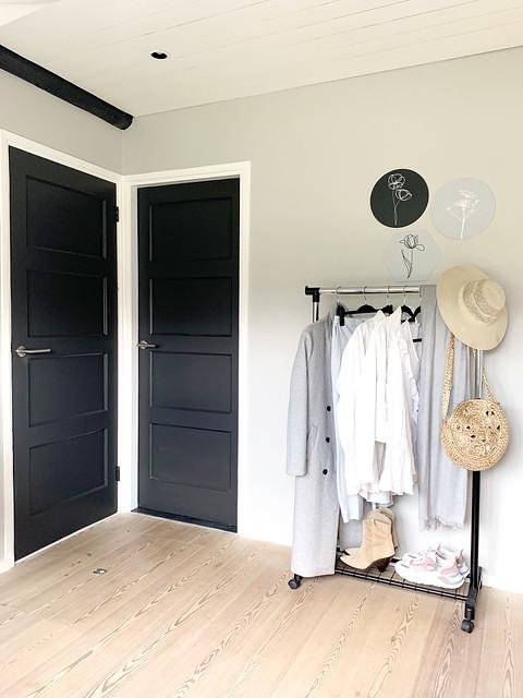 Zwarte deuren kledingrek strohoed muurcirkels met bloem slaapkamer