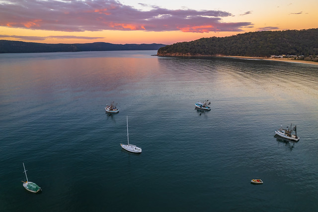 Peaceful sunrise over the bay with boats