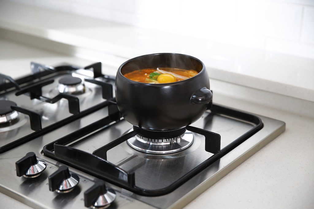 A modern style ttukbaegi filled with soup cooking on a stovetop.