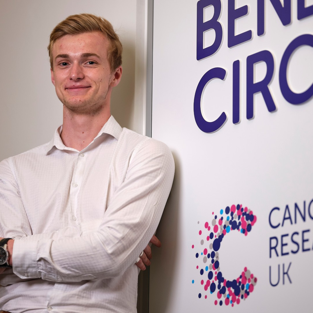 A young man smiling stood next to a Cancer Research UK logo on an office wall.