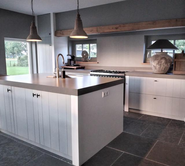 Landelijke keuken met houten balk en kookeiland kruiklamp met pet kap