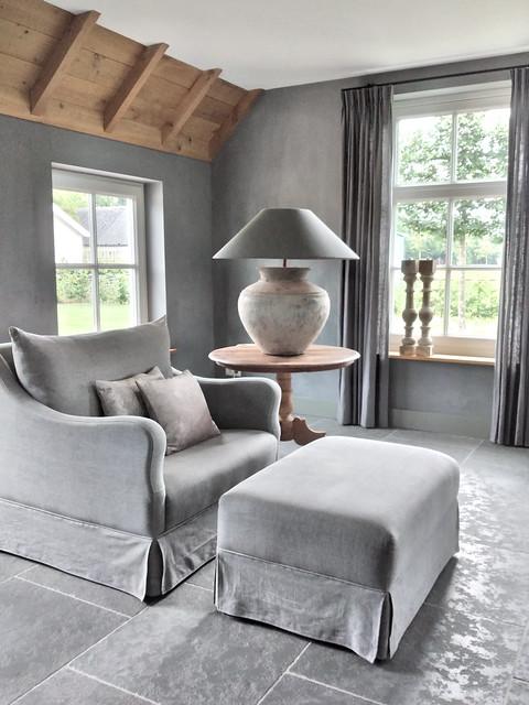 Kruiklamp met pet kap op wijntafel natuurstenen vloer woonkamer fauteuil met hocker
