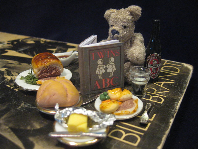 A Bear on a Book Reading a Book, Eating Beef and Bread with Butter, Drinking Beer!