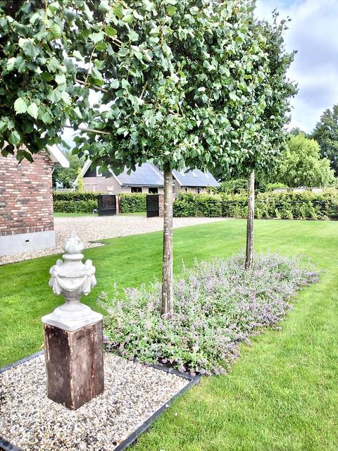 Klassieke tuinvaas op zuil landelijke tuin met tuinpoort