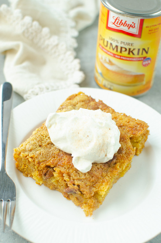 Pumpkin Crunch Cake on a white plate with whipped cream and cinnamon sugar on top
