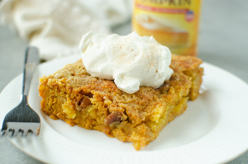Horizontal image of pumpkin cake on a white plate with whipped cream and cinnamon sugar on top; can of pumpkin puree and a cream colored napkin in the background