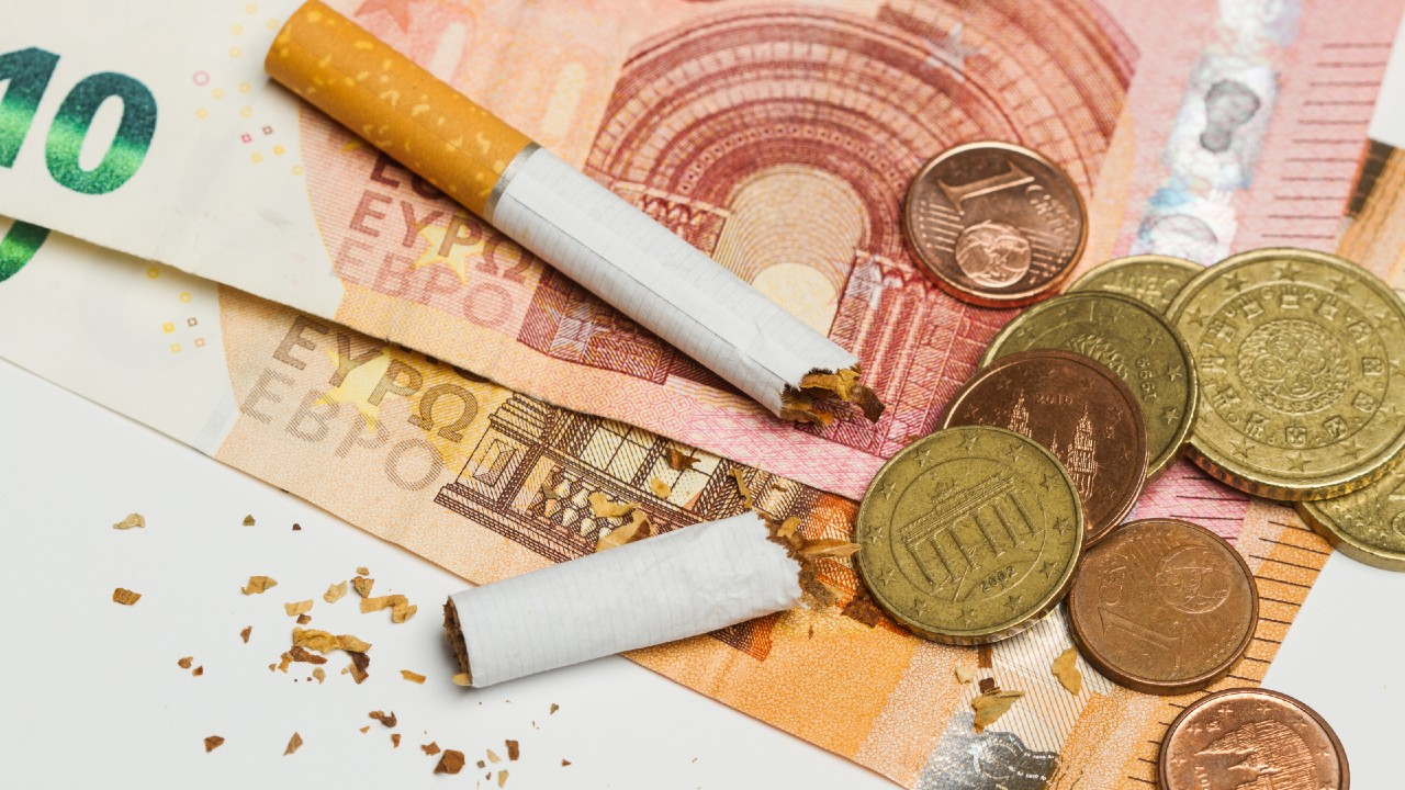 Broken cigarette with Euro coins and notes