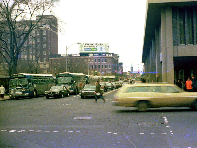 Buses drop people off at the New Haven Green near the  intersection of Chapel and Temple streets. The Chapel Square Mall at right.  The Union Trust bank offers a pewter mug for opening a savings account. A yellow station wagon zooms by. Dec 28 1974