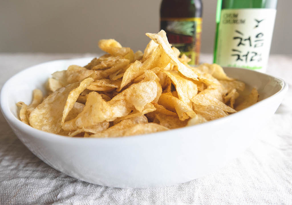A bowl of chips next to soju and beer.