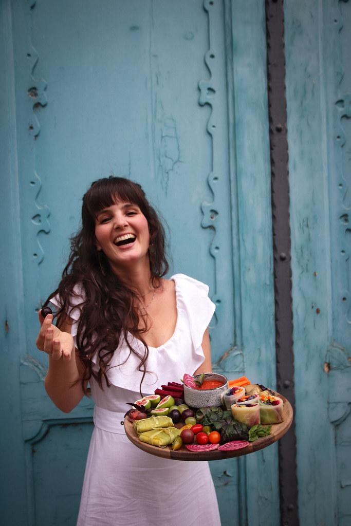 Kocsis Dóra a zero waste konyha szakácskönyv szerzője kék ajtó előtt nevetve fog a kezében gyönyörű szezonális étel tálat