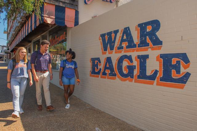 A group of Auburn students walk by the famed War Eagle wall near Auburn's campus