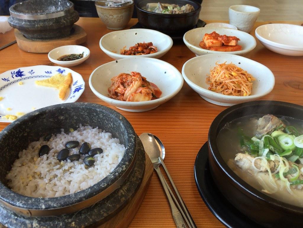 A table of Korean banchan, a dolsot of rice, and a ttukbaegi of soup.