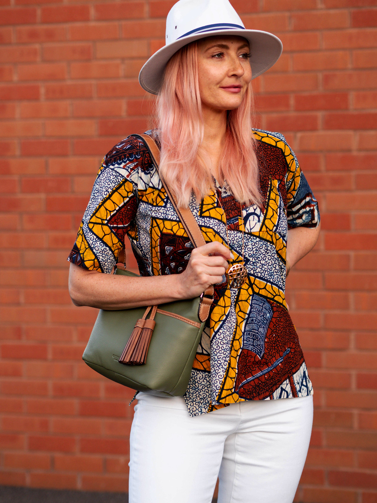 Catherine Summers AKA Not Dressed As Lamb wearing brown, yellow and navy vintage batik shirt, white jeans, white sandals, white cotton fedora with navy trim, olive Osprey London shoulder bag