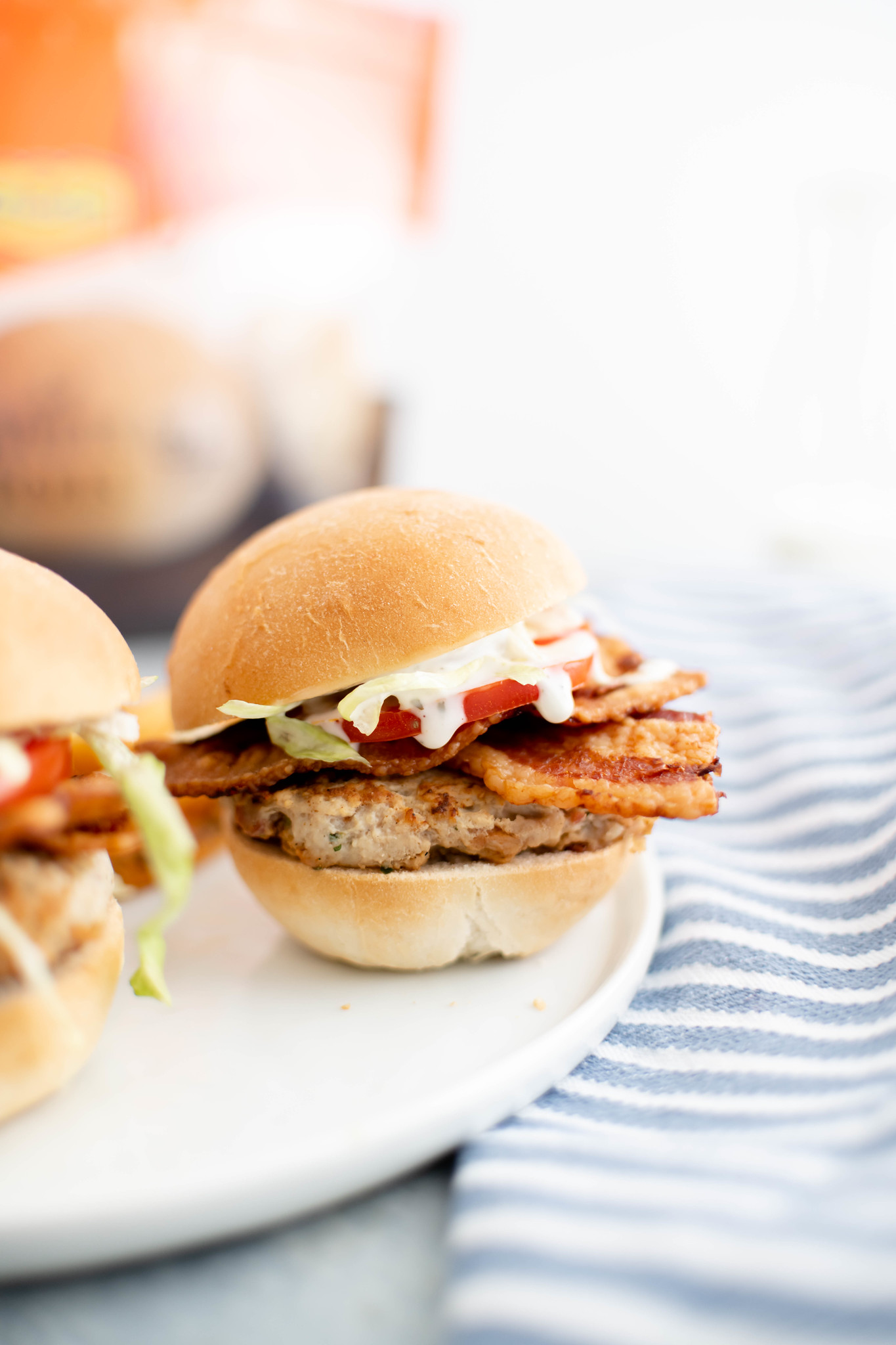 Close up of chicken bacon ranch slider on a white plate with a blue and white striped cloth napkin on the right.