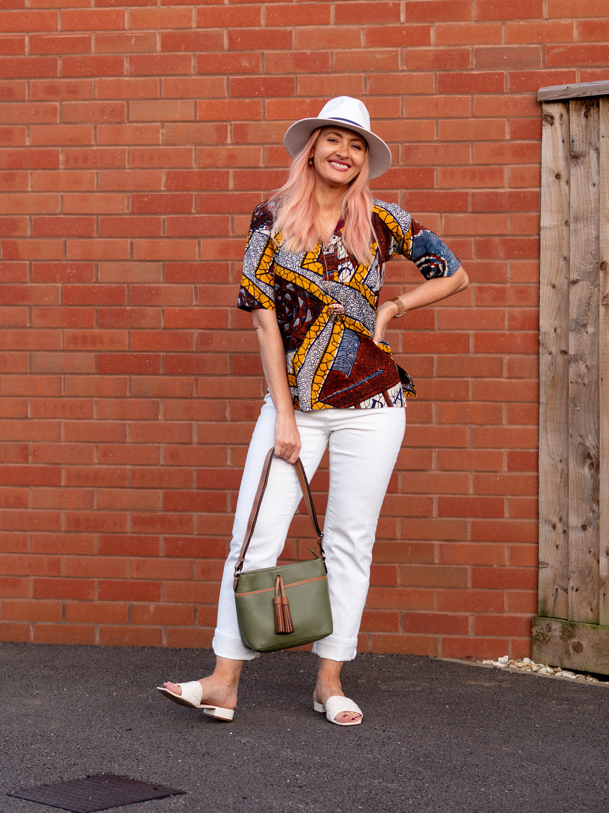 Ditching White Skinny Jeans For White Straight Leg Jeans: Catherine Summers AKA Not Dressed As Lamb wearing brown, yellow and navy vintage batik shirt, white jeans, white sandals, white cotton fedora with navy trim, olive Osprey London shoulder bag