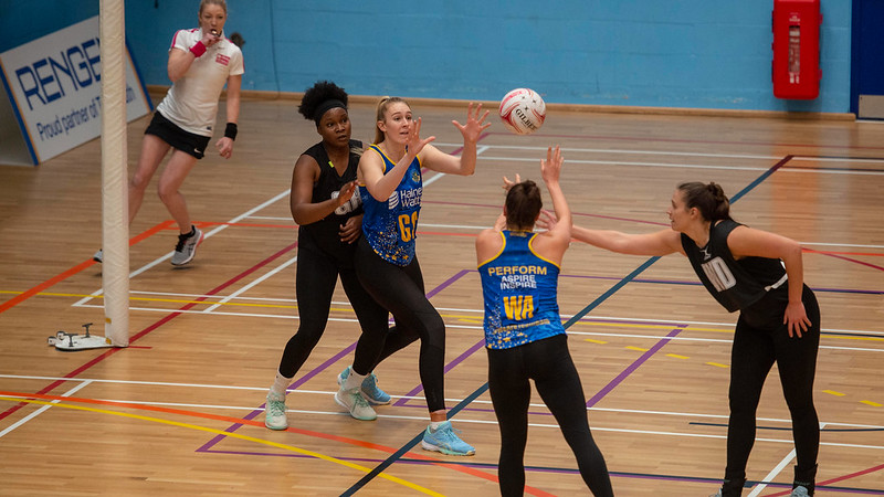 Three woman playing a professional game of netball.