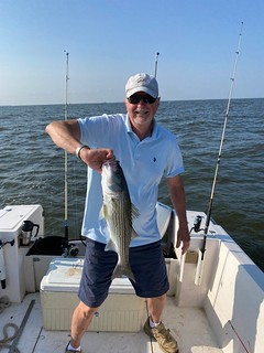 Photo of man on a boat holding a striped bass