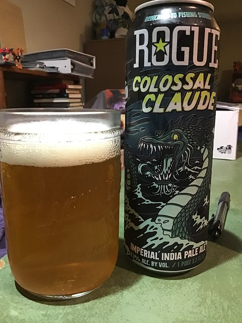 Rogue Colossal Claude IPA in glass on table next to can of same.