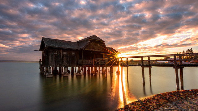 a lonely boathouse at a brilliant sunset