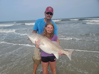 Photo of young girl and her father on a beach, holding a red drum fish
