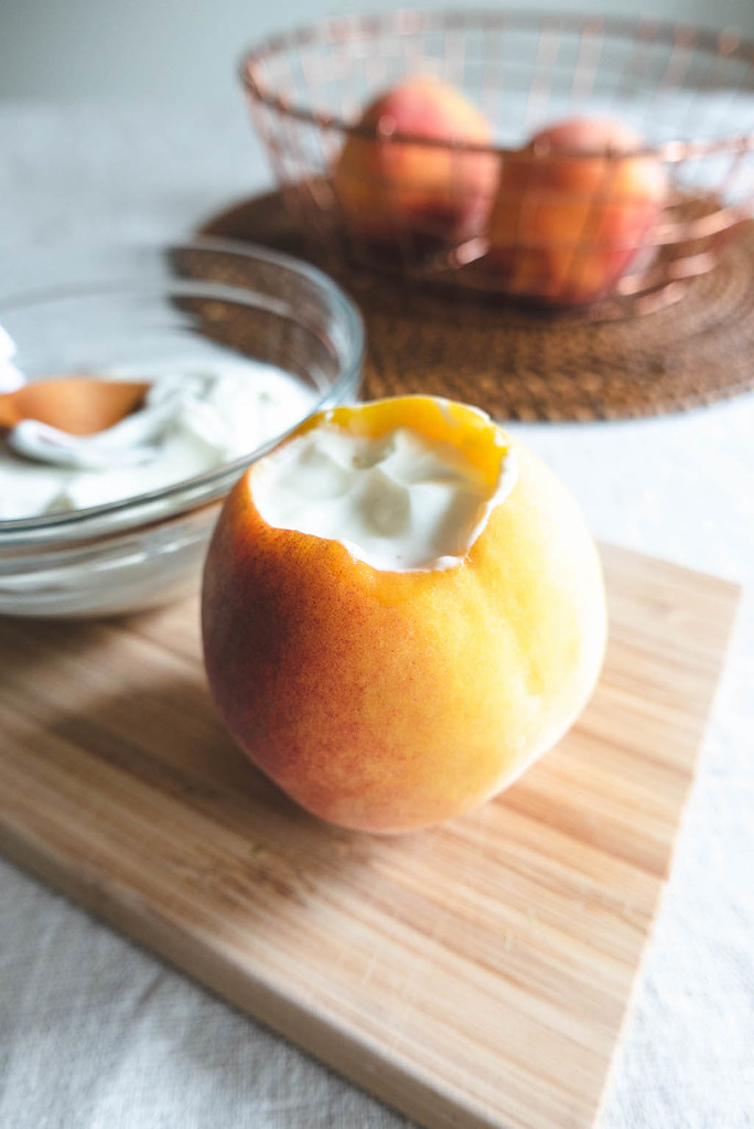 A side shot of a peach filled with yogurt.
