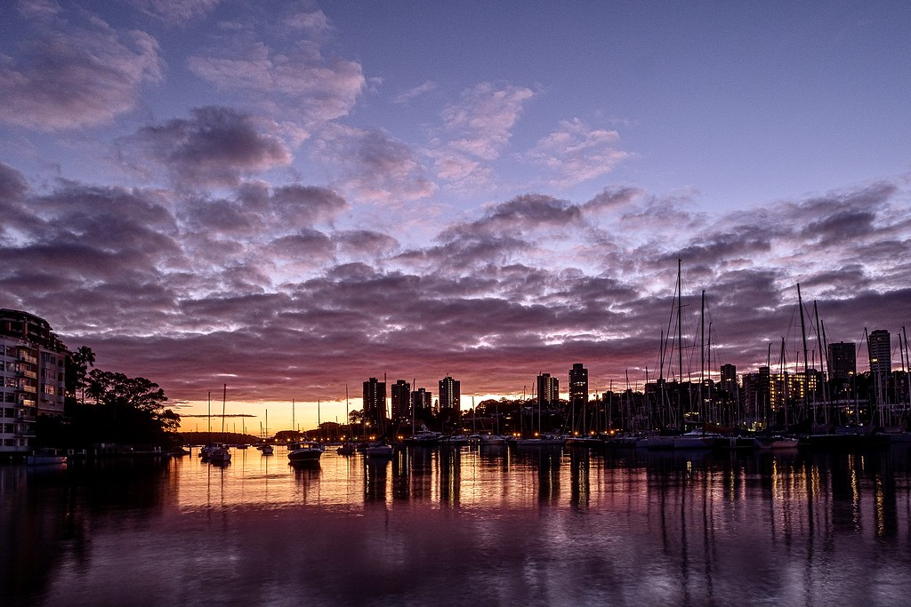 Light dawn clouds over Sydney Harbour seen from the shore of Rushcutters Bay.