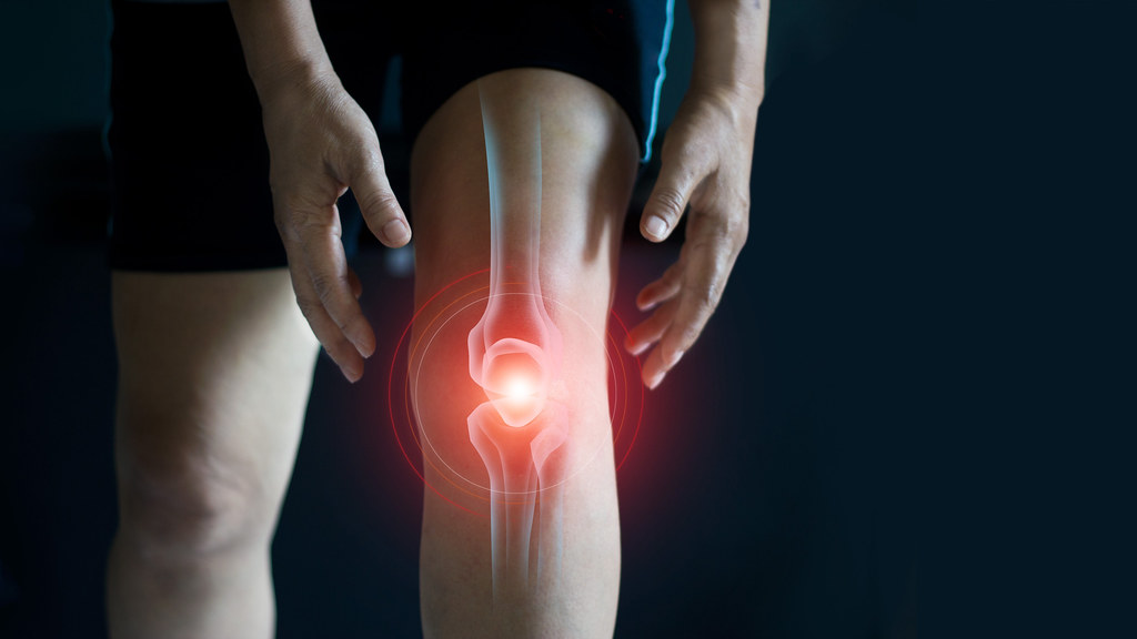 A man holding his knee in pain, digitally showing the bone and red colouring to indicate pain.