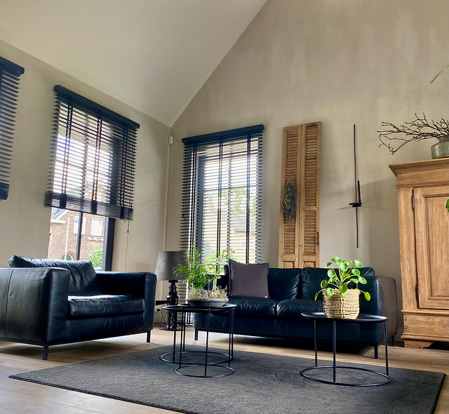 Boerderij stijl woning woonkamer kalkverf muren zwarte jaloezieën