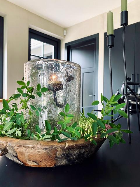 Houten schaal met windlicht van bubbelglas met hangkandelaar en groen