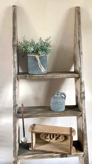 Houten ladder met kruikje hanglepel baksteenmal en plant in pot