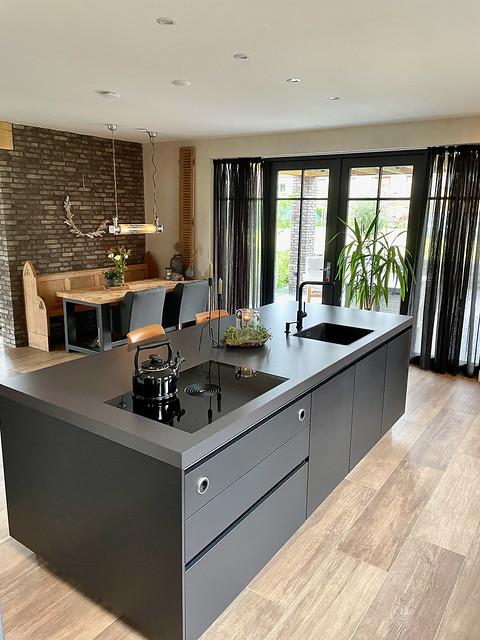 Zwarte strakke keuken zwarte tuindeuren en gordijnen schoonmetselwerk muur
