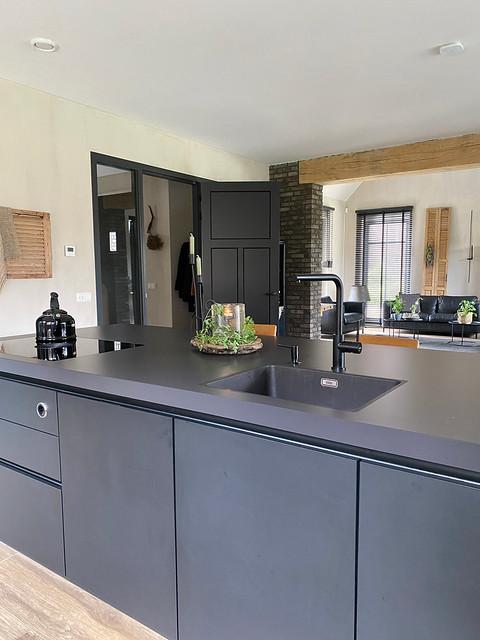 Zwarte strakke keuken met kookeiland in landelijk interieur