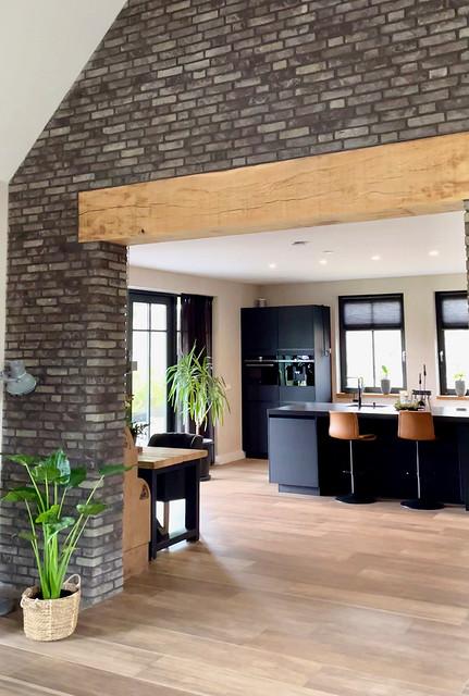 Boerderijstijl woning houten balk tussen keuken en woonkamer