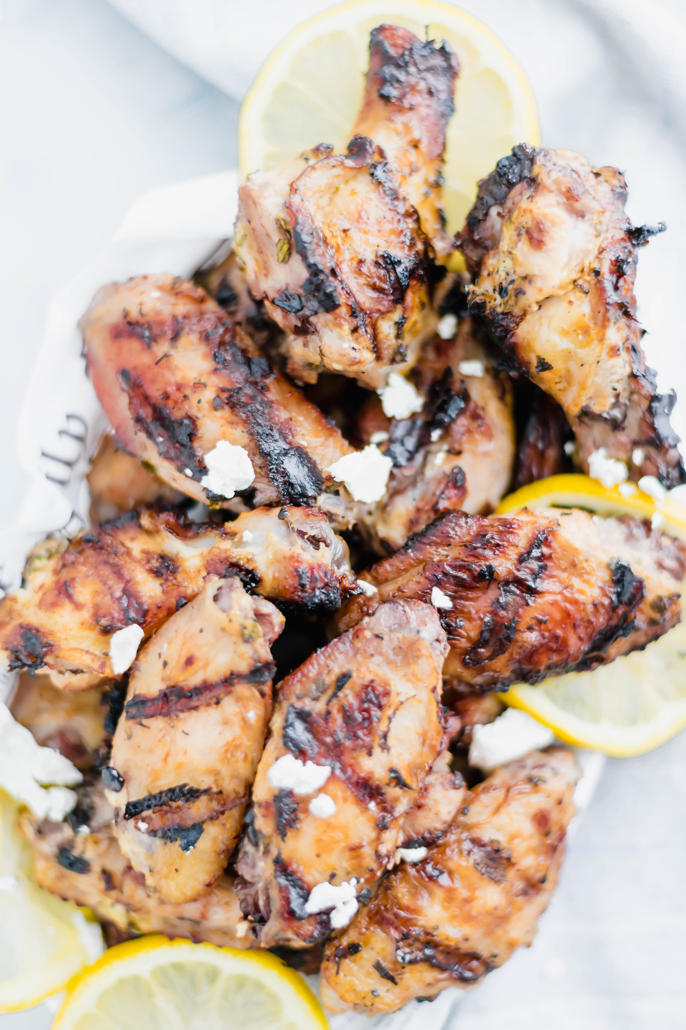 Don't let summer pass by without trying these grilled Greek Chicken Wings. Marinated in plain Greek yogurt, lemon juice and oregano, these wings are super juicy and bursting with bright flavor.