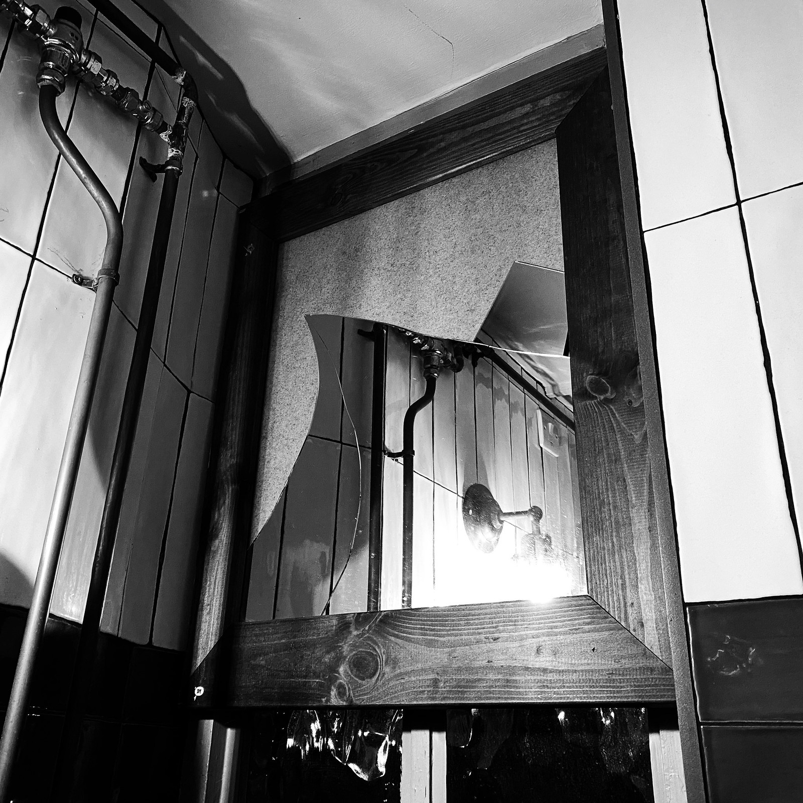 A black and white photo of a broken mirror on a tiled wall.