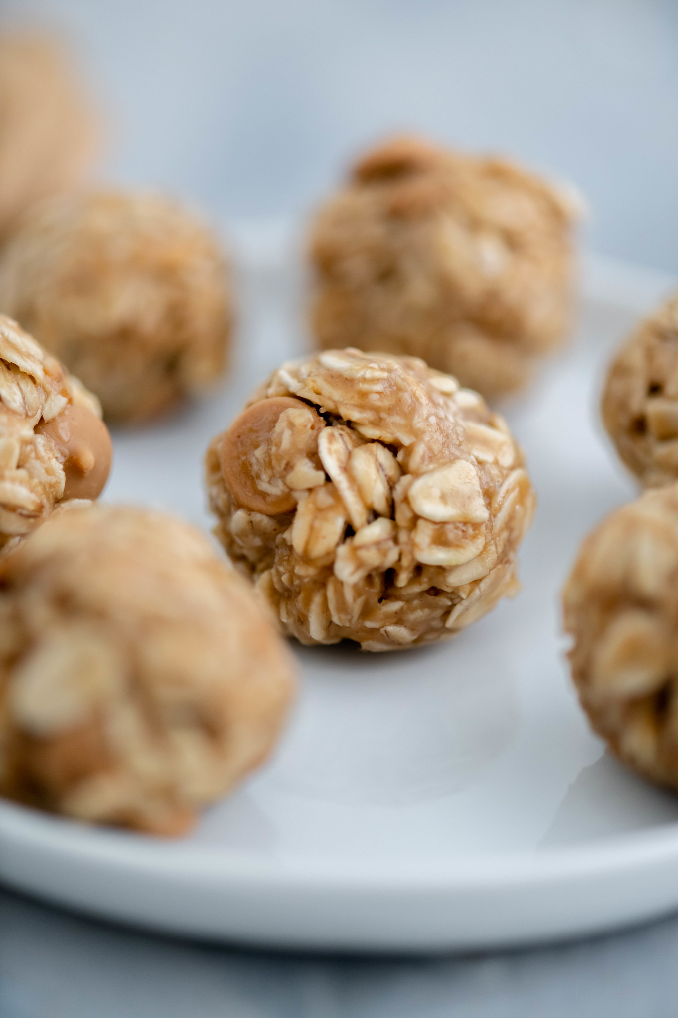 Close up shot of no bake peanut butter ball showing texture of oats and peanut butter chips.