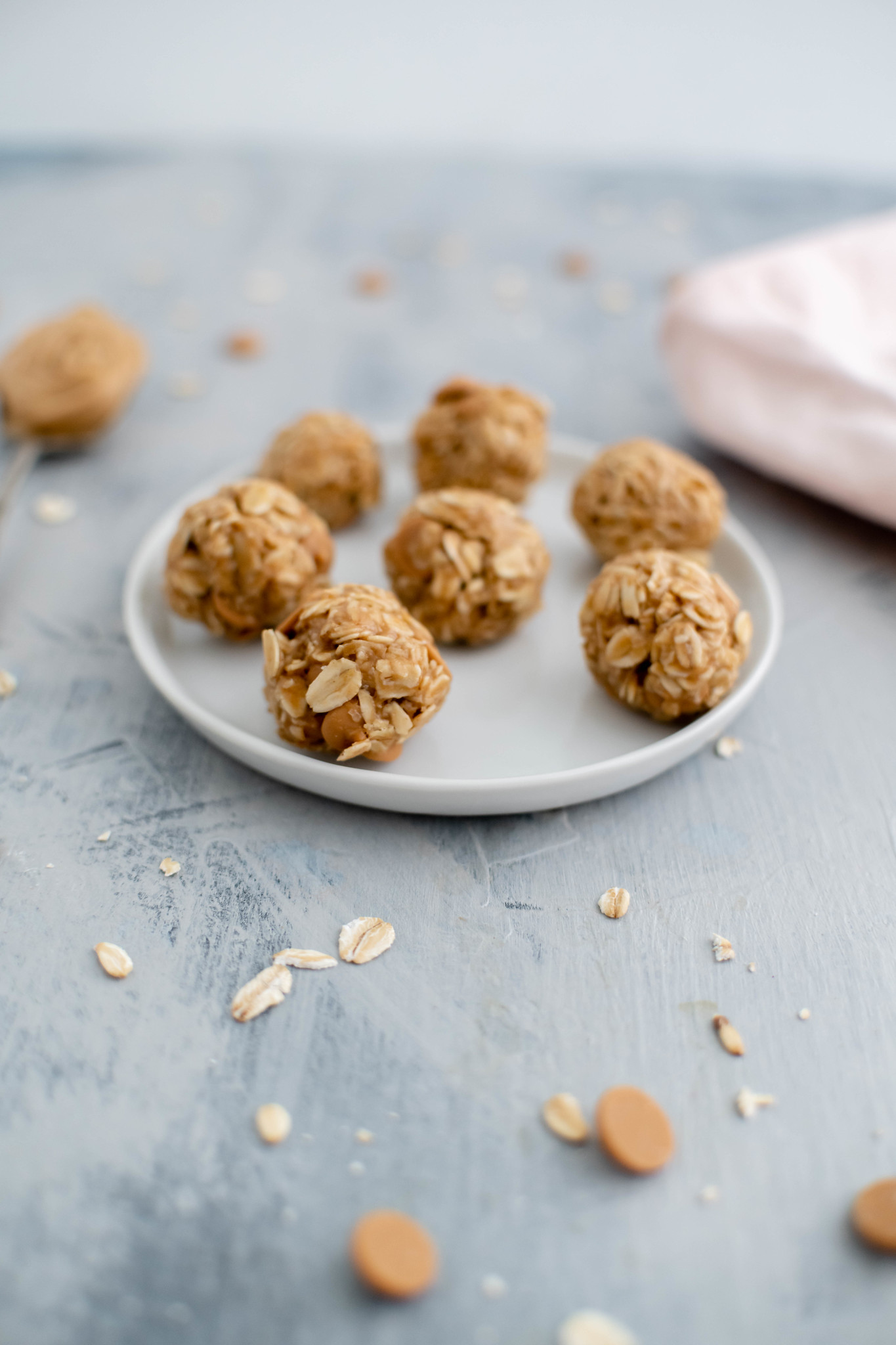 7 no bake peanut butter balls on a small white round plate. A spoonful of peanut butter in the background along with a pale pink cloth napkin.