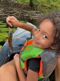 Photo of a girl in a kayak holding a small bluegill fish