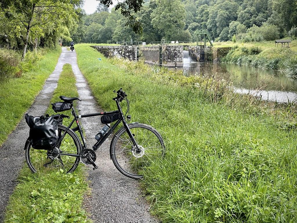 Le vélo de Tristan le long d'un canal avec une écluse