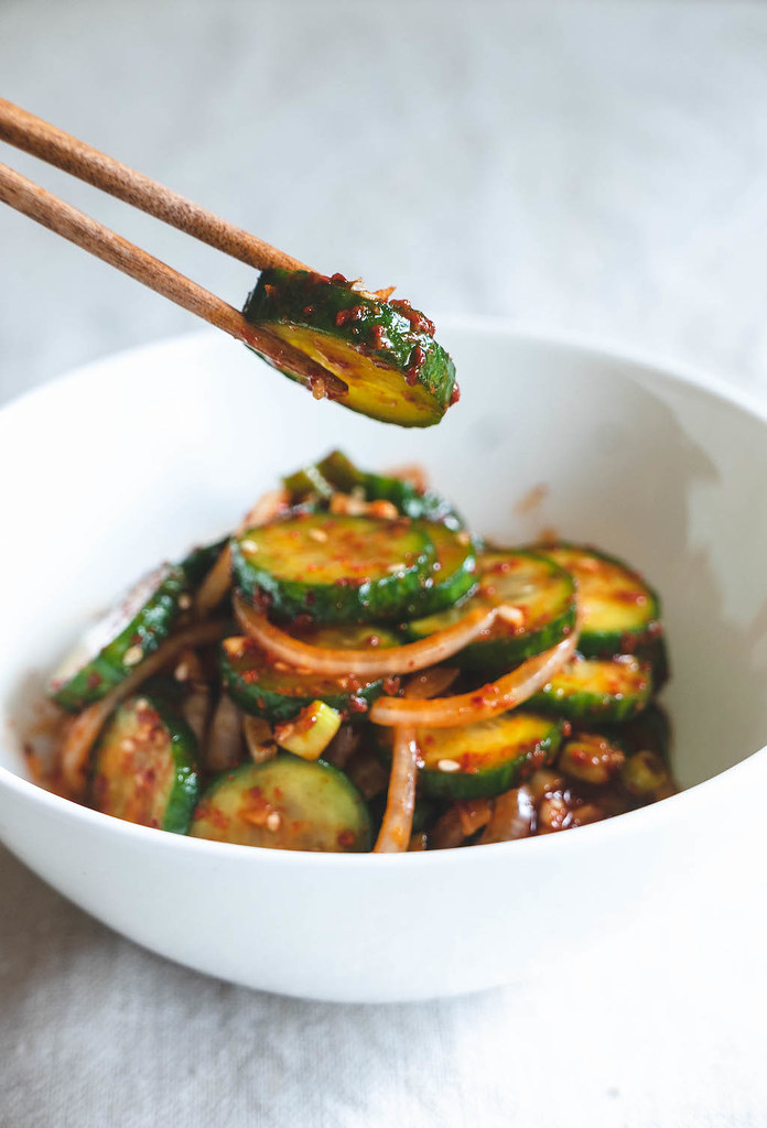 A photo of chopsticks holding some oi muchim. A bowl of the Korean cucumber salad in the background.