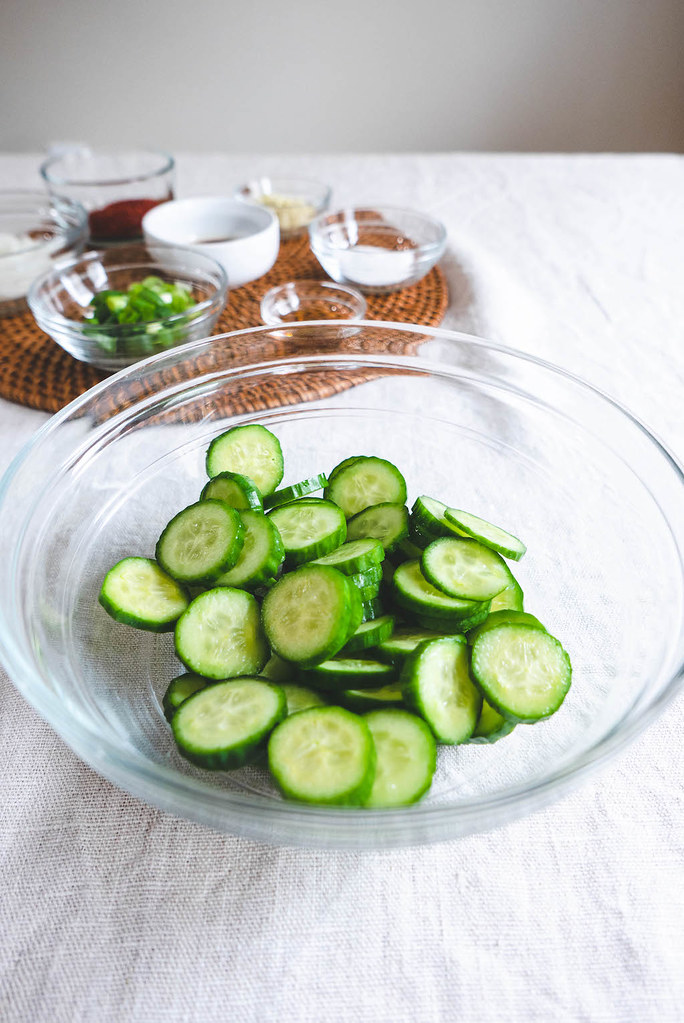 An overhead shot of cucumbers with the other Korean cucumber salad ingredients in the background.