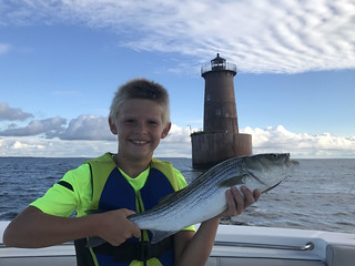Photo of a boy on a boat holding a striped bass, with a lighthouse in the background.