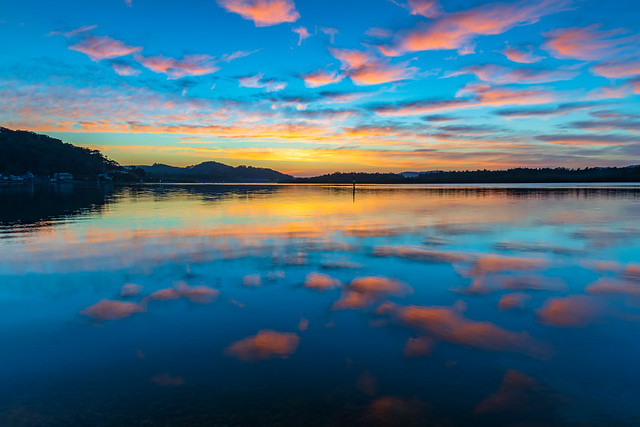 Sunrise waterscape with high cloud and reflections