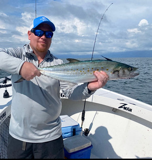 Photo of a man on a boat holding a Spanish mackerel